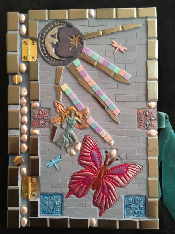 Image of a mosaic book cover featuring ceramic tile, polymer clay pieces and found objects.
