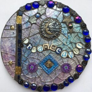 Image of a round mosaic book cover featuring glass, polymer clay pieces and found objects.
