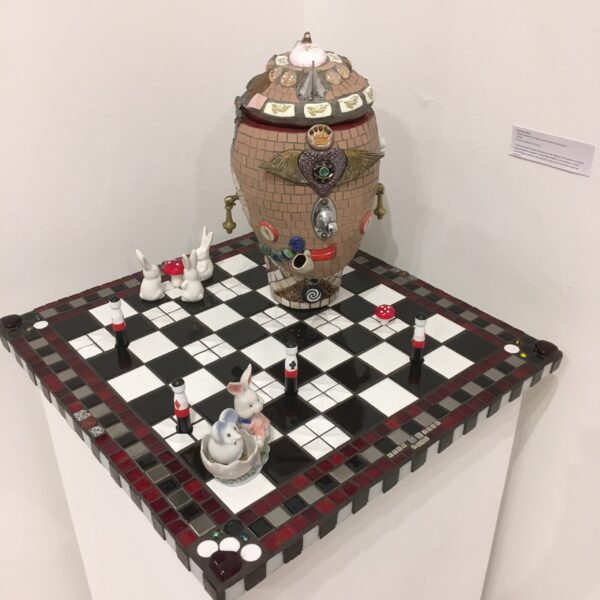 Image of a sculpture featuring a surreal head sitting on top of a chessboard surrounded by rabbits, toadstools and peg figures.