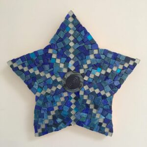 A pretty star-shaped mosaic made with blue smalti, silver glass and vintage button inset into polymer clay in the centre.