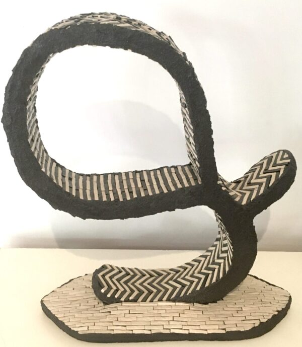Image of a black and white ceramic mosaic sculpture in an abstract form.