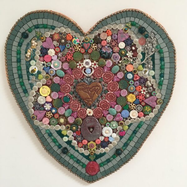A heart-shaped mixed media mosaic with a flower shape in the middle. The mosaic features some beautiful vintage buttons, jewellery and handmade polymer clay millefiore.