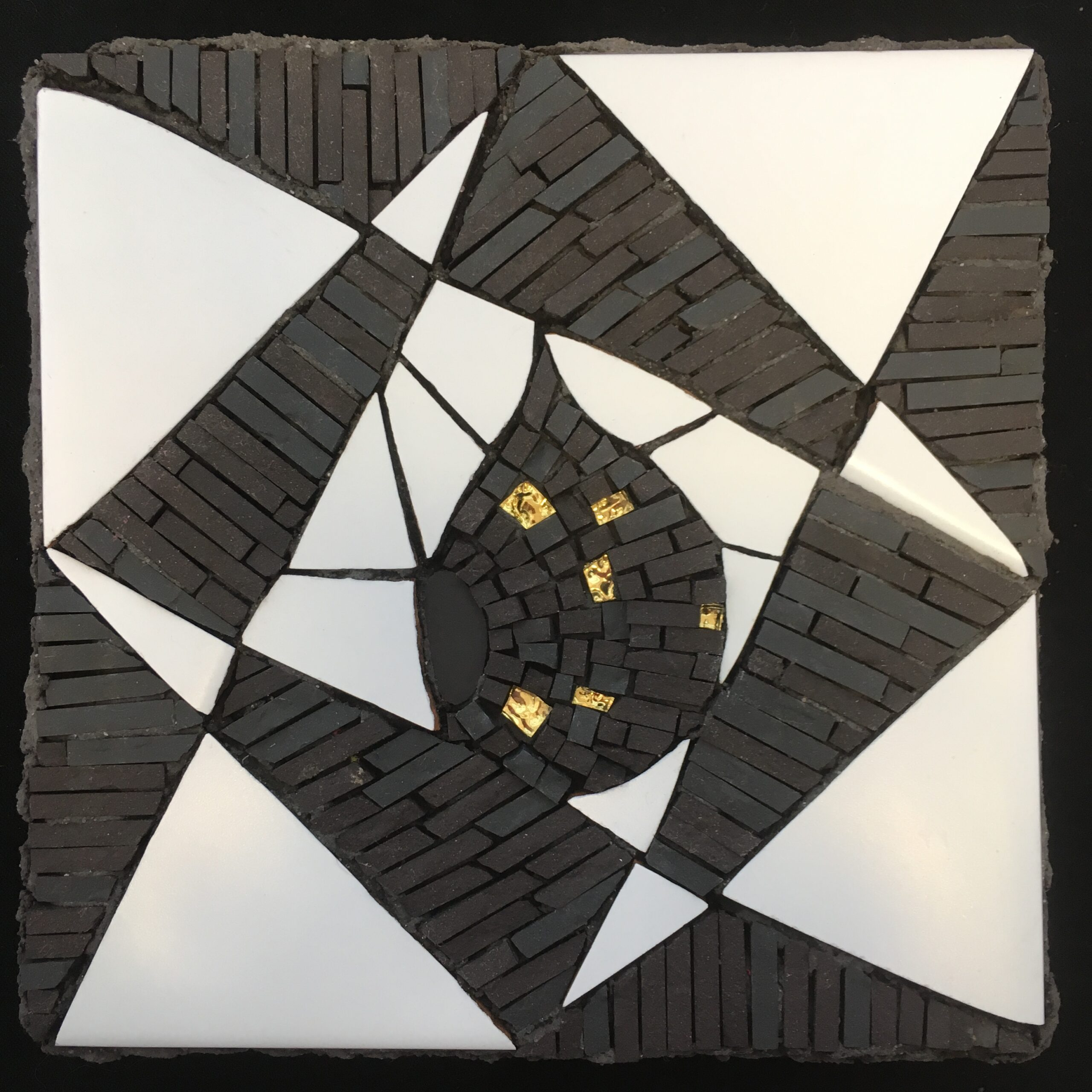 Image of a small black and white mosaic of geometric shapes featuring a central teardrop shape with gold glass pieces inserted.