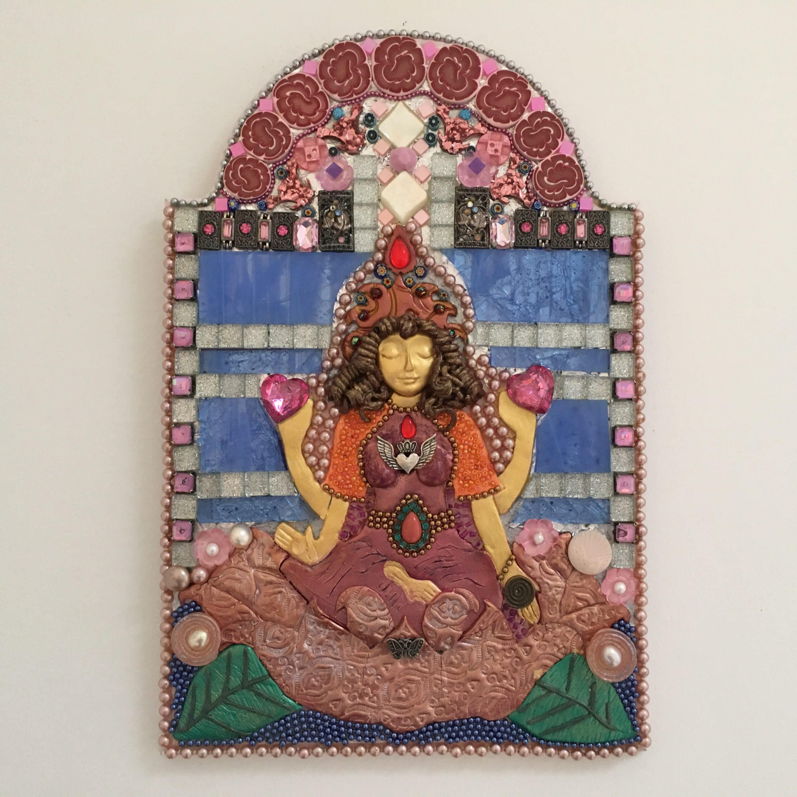 A mixed media mosaic featuring a central female figure with four arms who is seated on a lotus lflower and offering gifts from her hands.