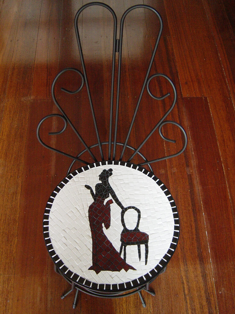 An upcycled wire chair with a red figure