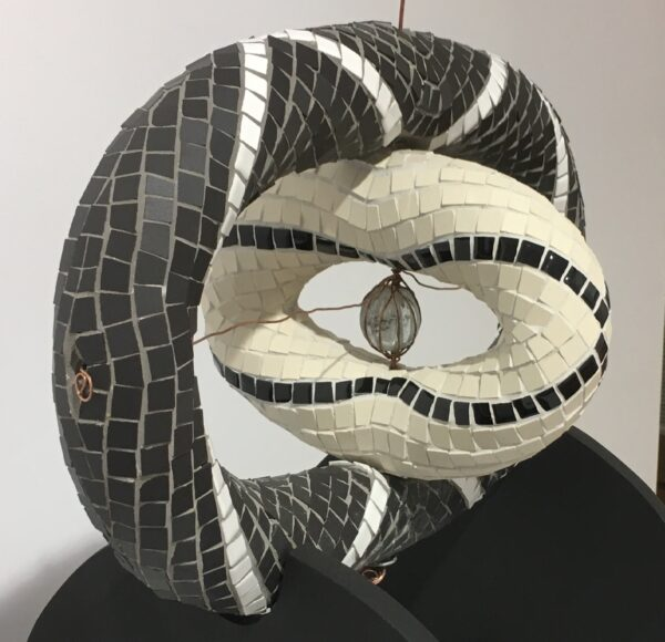 Image of a mosaic sculpture in black and white ceramic tile with copper wire and a glass bead centre. The sculpture has two main parts at perpendicular angles to each other.