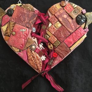 Image of a heart-shaped mixed media work featuring polymer clay pieces and found objects.
