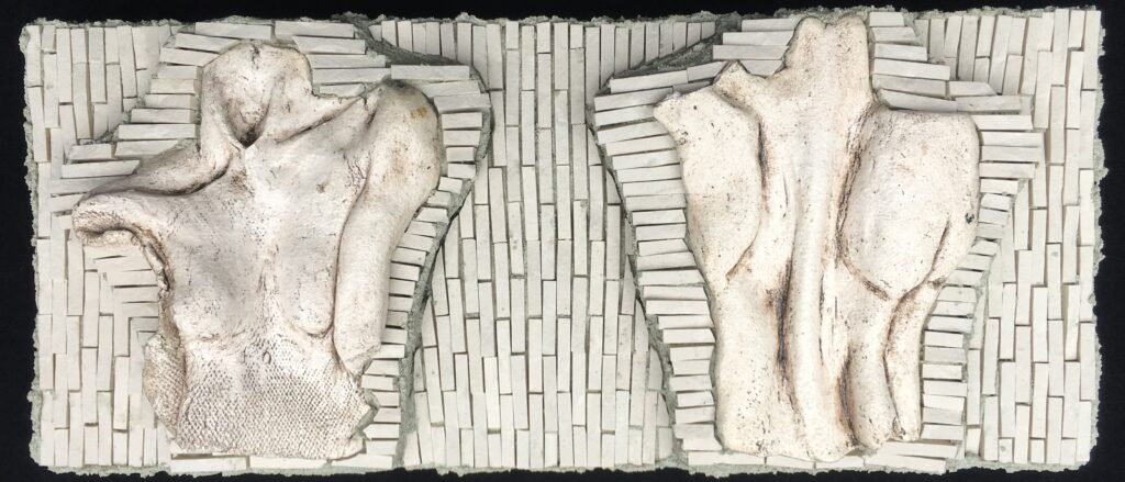 A white mosaic featuring some ceramic figurative elements