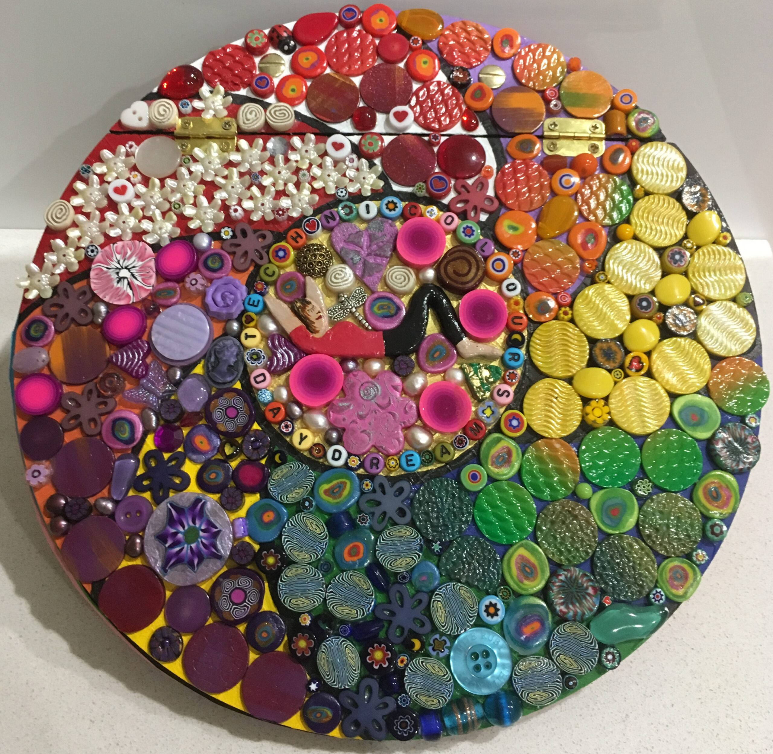 Image of a round mosaic book cover featuring polymer clay pieces and found objects.