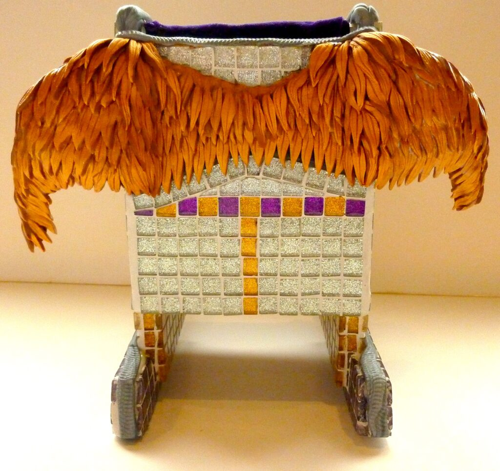 Back view of a small rocking chair covered in glitter tile mosaic and sporting a pair of out-stretched gold wings.