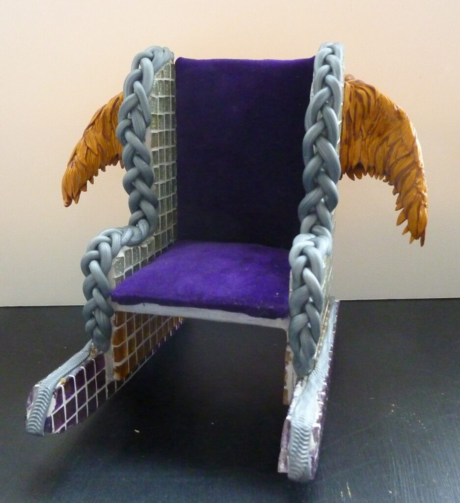 Front view of a small rocking chair with glitter mosaic tiles, purple fabric and gold wings.