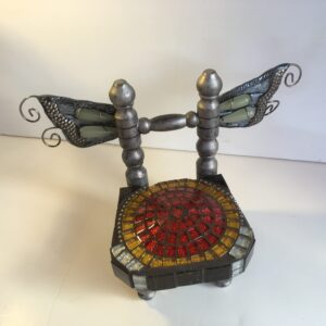 Front view of a small chair sculpture with silver butterfly wings and a red glitter mosaic seat.