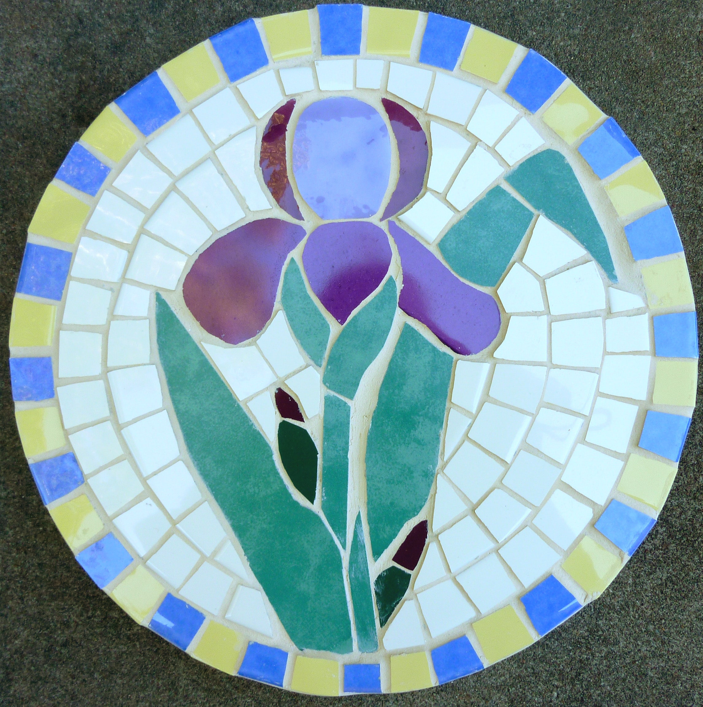 Image of a round ceramic mosaic featuring a purple iris.