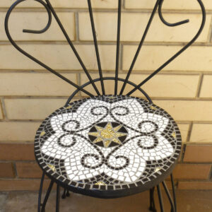 A repurposed wirework chair with a decorative mosaic seat in back, white and gold mosaic