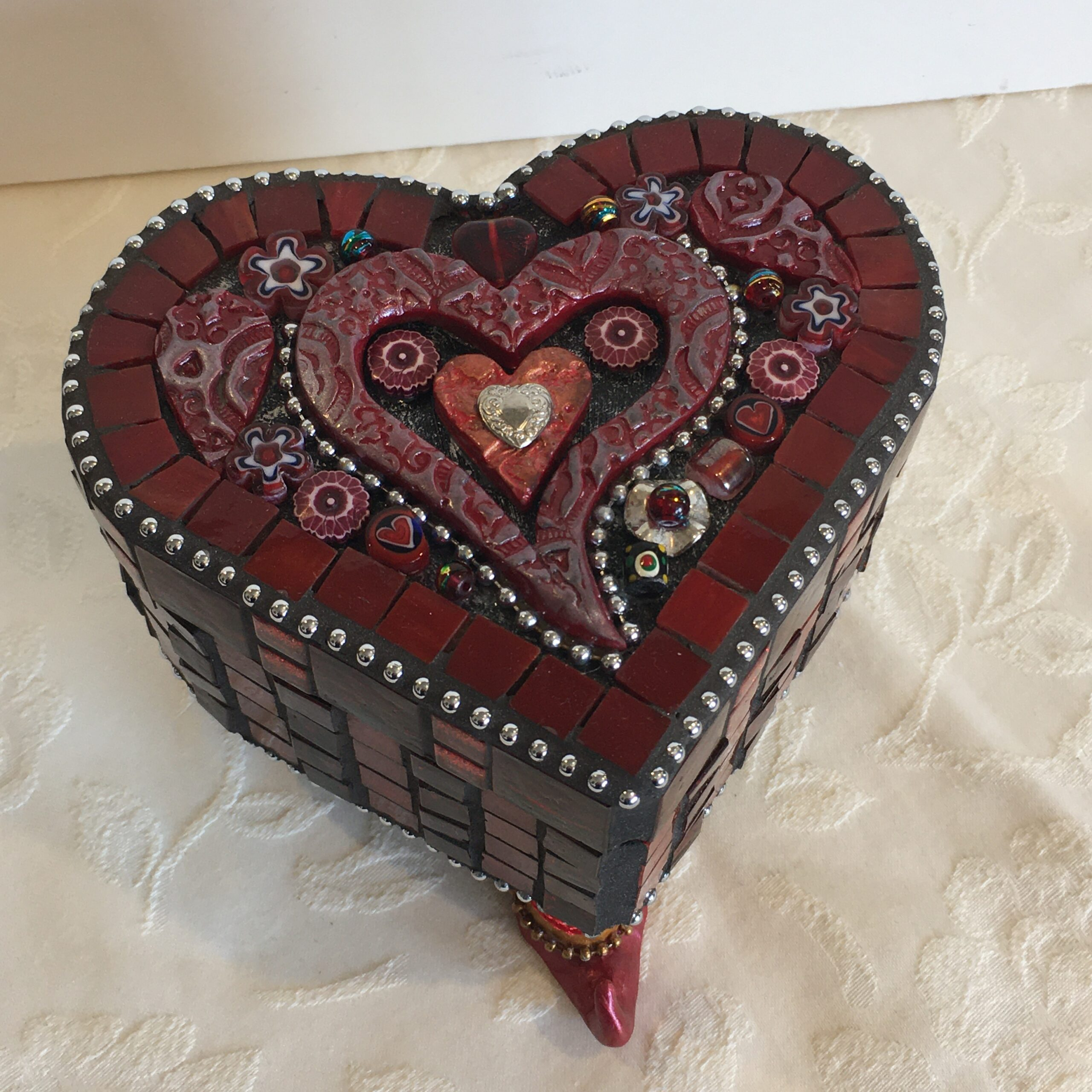 A heart-shaped box with Genie boot feet and decorated with polymer clay, glass mosaic and found objects.