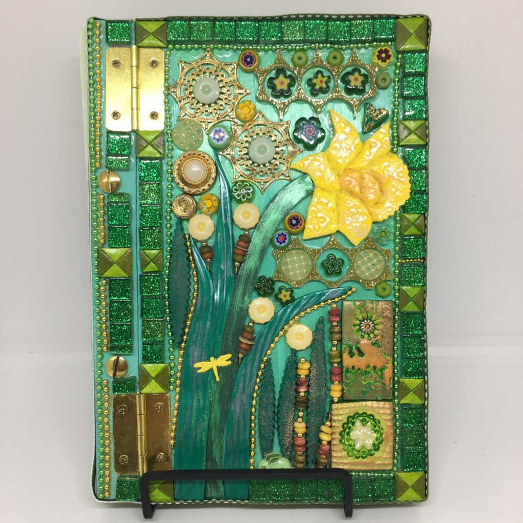 An A5 art journal with a Spring theme, featuring a bright yellow daffodil and mixed media in green and gold.