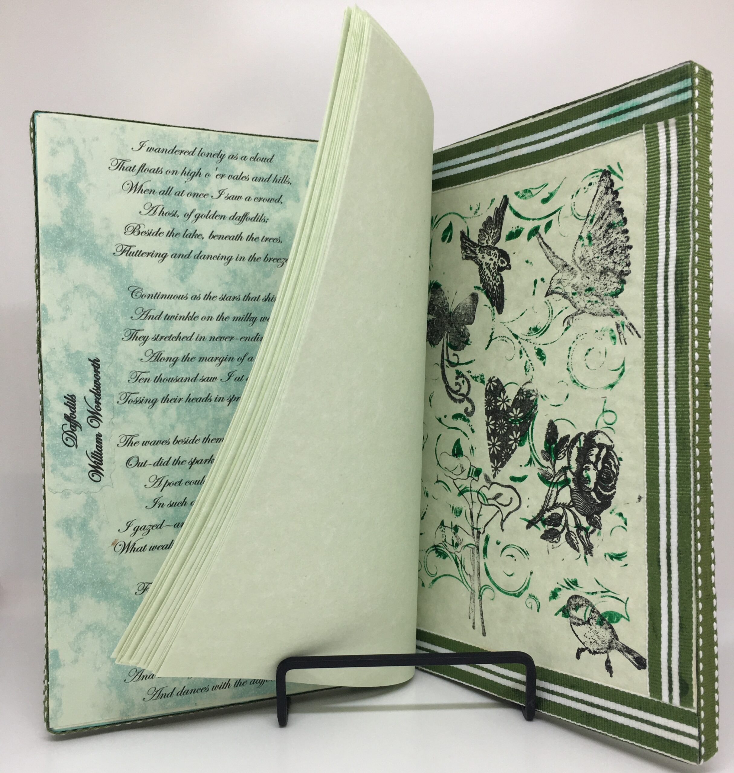 Internal view of Daffodil Days art journal, featuring pale green blank pages and green and white ribbon.