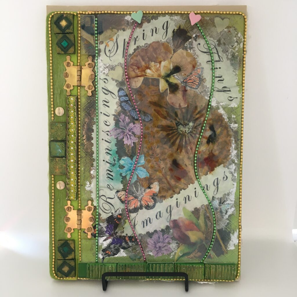 Front cover of an A4 art journal featuring collage of butterflies and flowers under clear glass.